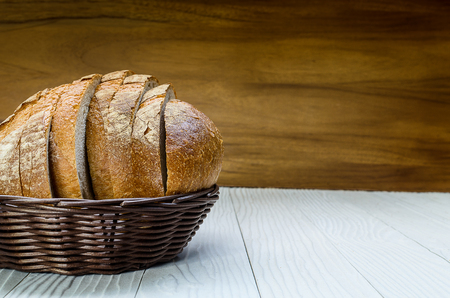 A Sliced Pain De Campagne Au Levain Bread in the wicker brown wood basket bowl.