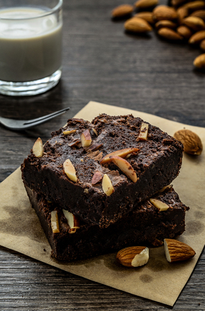 Chocolate Brownie with Almonds on the wood table has ready to served in the dessert time.