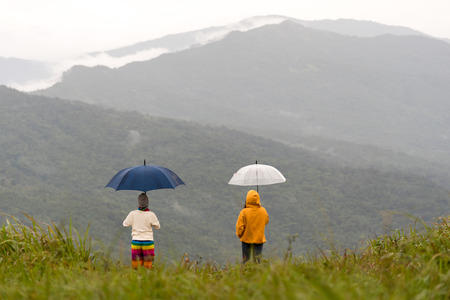 Duo female hiker holding umbrella and relaxing with big mountain and heavy mist under the cloudy sky.