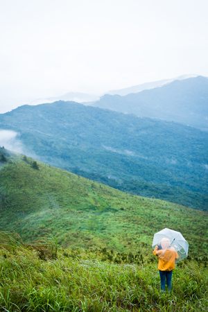 Alone female hiker holding umbrella and relaxing with big mountain and heavy mist under the cloudy sky. Stock Photo
