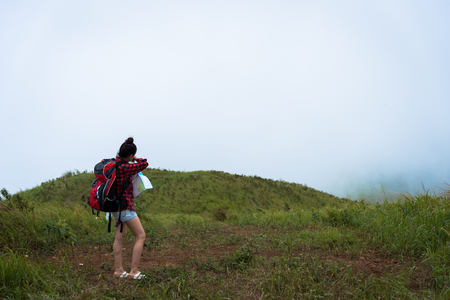 Alone Girl with red overcoat and blue jeans has looking for way to the mountain in the heavy mist and cloudy. Stock Photo