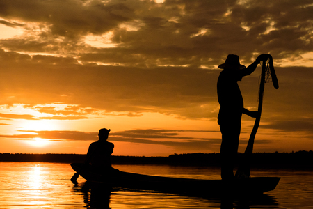 Silhouette of Fishermen with sunset time at Wanon Niwat district Sakon Nakhon Northeast Thailand.