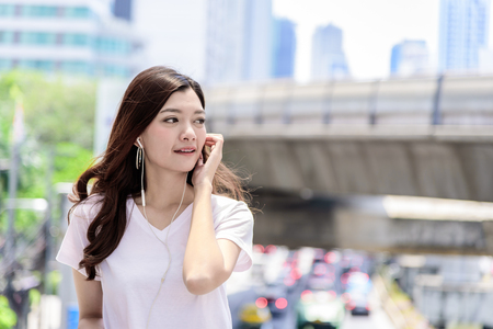 Asian beautiful woman tourist has music listening with headphone and happiness to travel. Stock Photo