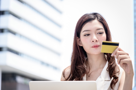 The asian business woman has shopping and buying with credit card from outside office with building and city background.