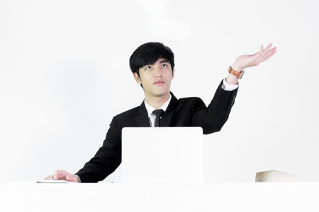 Asian manager businessman sitting at desk throwing papers with feeling angry and upset, isolated on white background.
