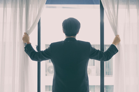 Asian manager businessman has opening window and curtain with feeling hopeful with lighting in the morning.