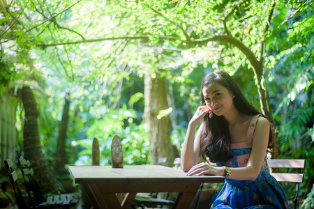 Asian pretty girl has relaxing with happy and smiling at Little Tree Garden cafe, Nakhon Pathom province, Thailand in the morning.