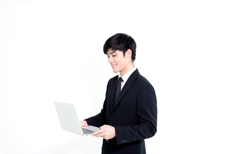 Asian business handsome man has holding laptop for woking with happy and relaxing isolated on white background. Stockfoto