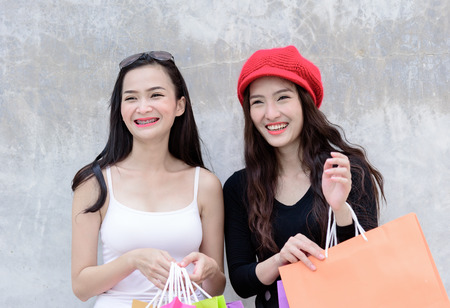 Duo asian portrait girl has happy and smiling with shopping colorful bags and grey wallpaper background.