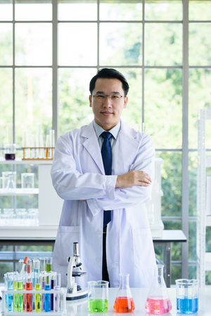 Asian Laboratory scientist man working at lab with test tubes.