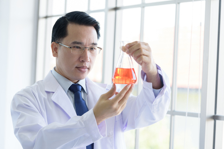 Asian Laboratory scientist man working at lab with test red tubes.