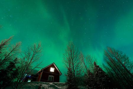 The northern lights Aurora Borealis at Kuukiuru village lake in Lapland, Finland. 免版税图像