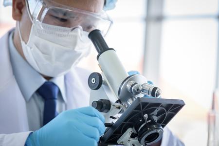 Científico asiático investigando y aprendiendo en un laboratorio.
