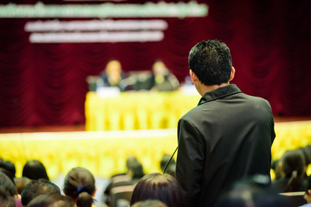 Asian business man holding microphone on conference and speaking into the microphone and looks to the coach.
