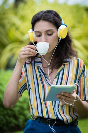 Portrait of a beautiful woman has drunk a coffee and listening to music with smiling and relax in the garden.