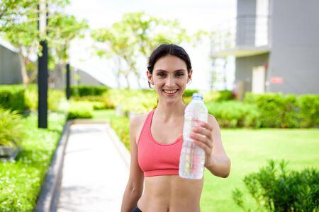 Beautiful woman runner has drinking water in the garden. Zdjęcie Seryjne