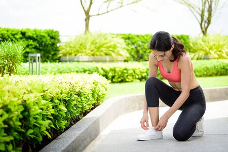 Beautiful woman runner has to tie white shoelaces in the garden.