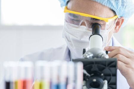 Asian young man student scientist researching  and learning in a laboratory. Banco de Imagens