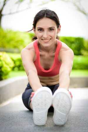 Beautiful woman runner has to warm up with stretching in the garden.