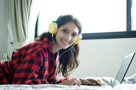 Beautiful woman working and listening to music on a laptop with yellow headphone and lying down on the bed at a condominium in the morning.