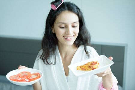 A beautiful woman wearing a towel and a white bathrobe has to eat a pizza and sliced tomato with happy and relaxing on the bed at a condominium in the morning. Imagens