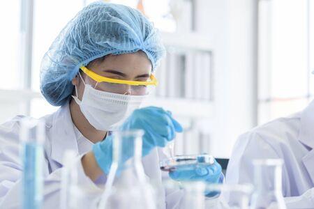 Científico asiático joven estudiante investigando y aprendiendo en un laboratorio. Foto de archivo