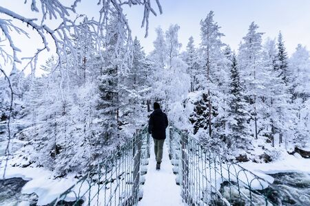 Tourist has walking alone in the forest with heavy snow covered and bad weather sky in winter season at Oulanka National Park, Finland.
