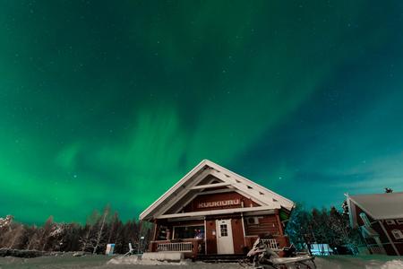 The northern lights Aurora Borealis at Kuukiuru village lake in Lapland, Finland. Redakční