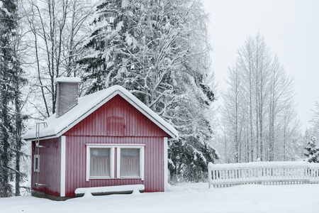 The house in the forest has covered with heavy snow and bad sky in winter season at Holiday Village Kuukiuru, Finland.