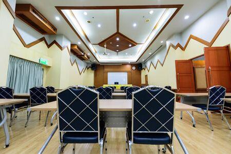 La grande salle de réunion vide avec de nombreuses chaises.