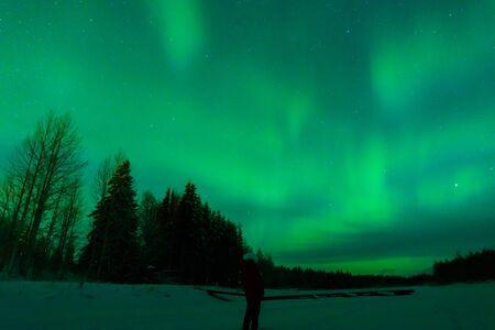 People has looking the northern lights Aurora Borealis at Kuukiuru village lake in Lapland, Finland.