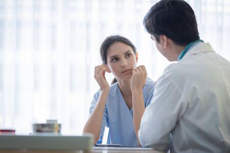 Un médico atiende a una paciente enferma con tristeza e infelicidad en el hospital o clínica médica.