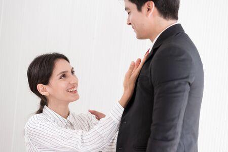 Esposa atar la corbata roja a su marido en la oficina con una sonrisa y feliz.