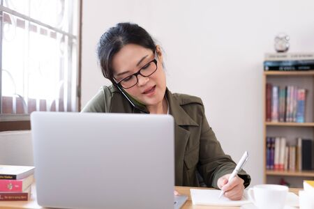 Modern young Asian woman working from home.