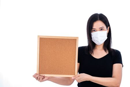 An Asian woman holding an empty board for writing COVID-19 prevention isolated on white background. Фото со стока