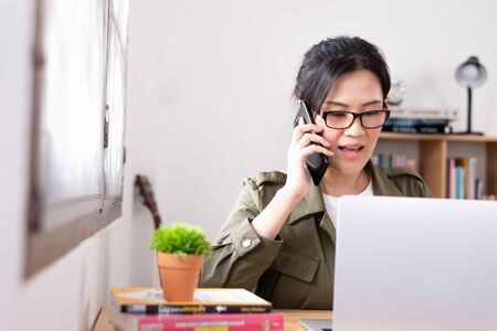 Modern young Asian woman working from home and talking with a partner about her business. Фото со стока