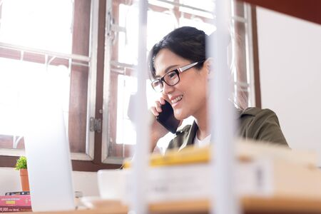 Modern young Asian woman working from home and talking with a partner about her business with happy and smile. Фото со стока
