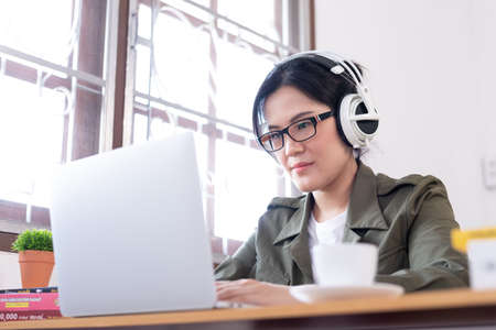 Modern young Asian woman working from home and listening to the music with a white headphones.