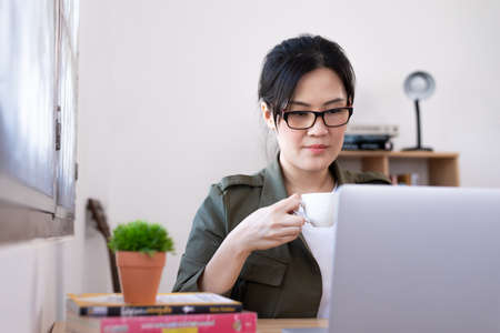 Modern young Asian woman working from home and drinking a coffee. Фото со стока