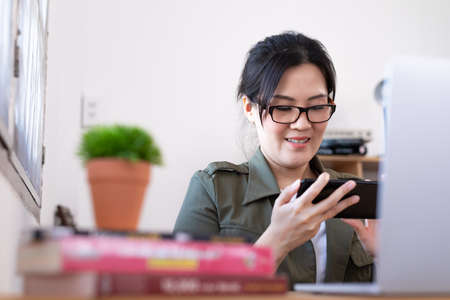 Modern young Asian woman playing a game instead of working from home with happy and fun.