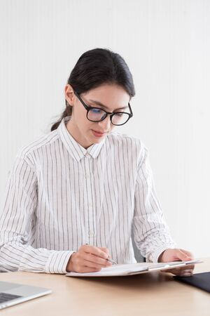 A businesswoman wearing glasses working with smiling and happiness at the office.