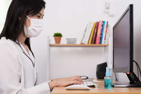 A beautiful Asian businesswoman wearing a mask and cleaner gel to protect COVID-19 before start working from home with safety and happiness. Фото со стока