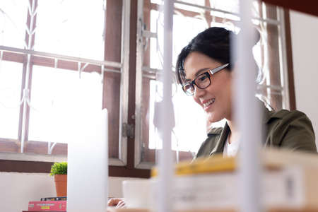Modern young Asian woman working from home with happy and smile.