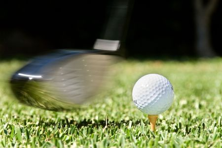 Golf club being swung at golf ball during a competition photo