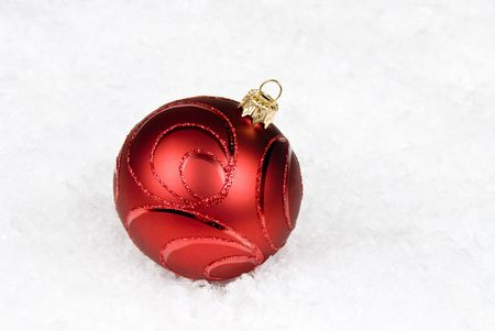 Lone ornament rests in the snow photo