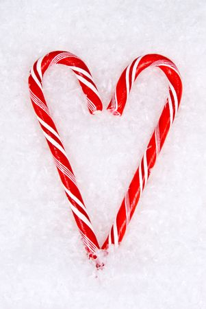 Candy cane heart sits in the snow symbolizing love photo