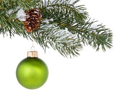 green christmas tree ornament hangs from a pine tree branch on a white background stock photo