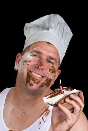 A chef examines his gourmet birthday creation consisting of burnt toast, chocolate and vanilla icing and a candle. Stock Photo - 1943130