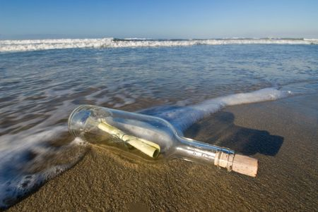 A bottle with a message inside of it washes ashore for a lucky person to discover. Stock Photo