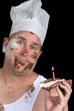 A chef shows off his failed cake consisting of a piece of burnt toast, with chocolate and vanilla icing and a birthday candle.  Stock Photo - 1943137
